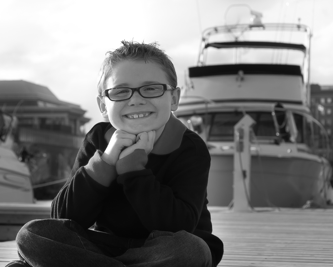 portrait of a young boy in front of a boat, marina park, thunder bay